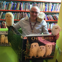 A member of library staff with a big Owl Babies book