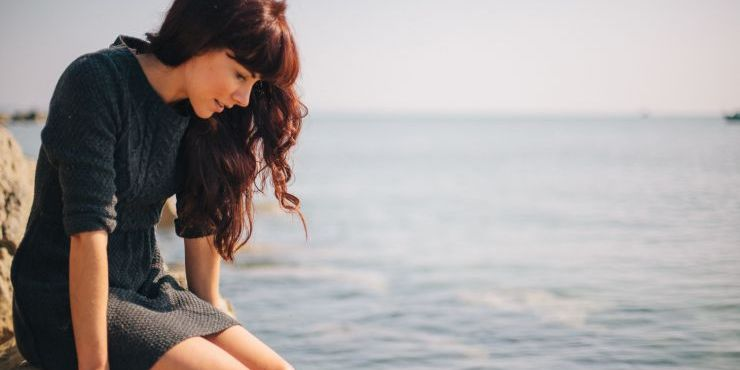Image of Lucy Clarke looking down at the sea sitting on a rock